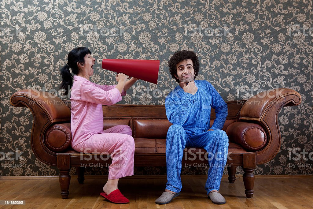 House Wife Shouting At Husband Via Megaphone On Sofa royalty-free stock photo