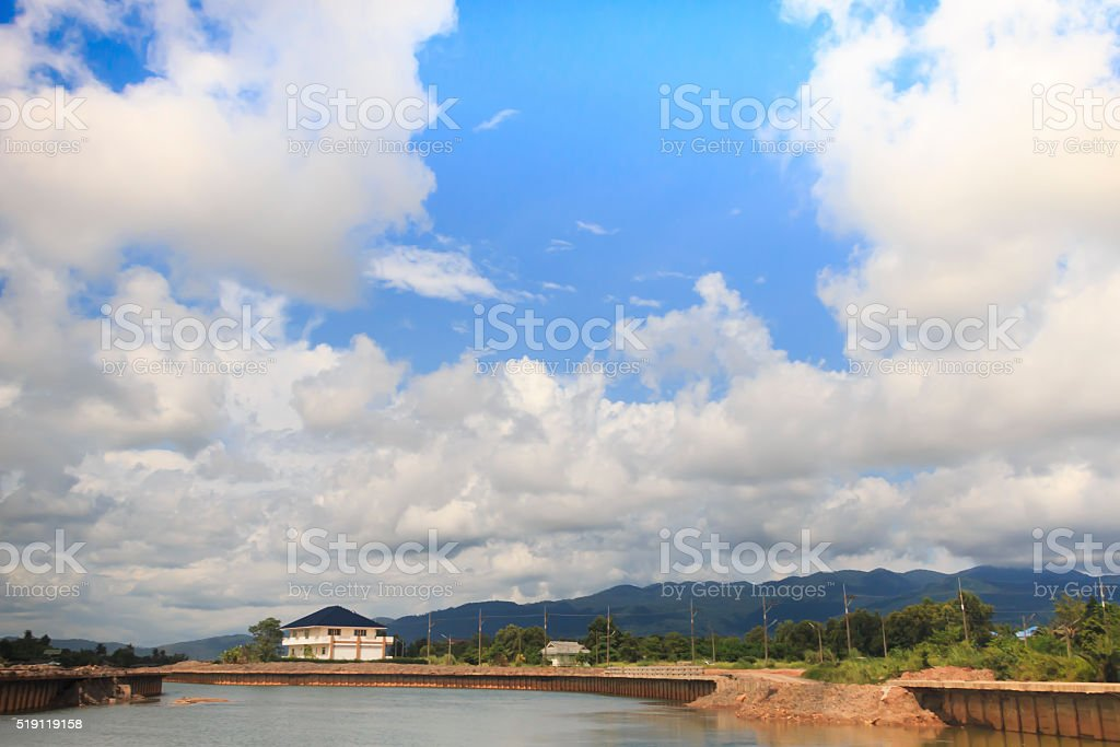 House with clouds on the opposite shore of the lake stock photo
