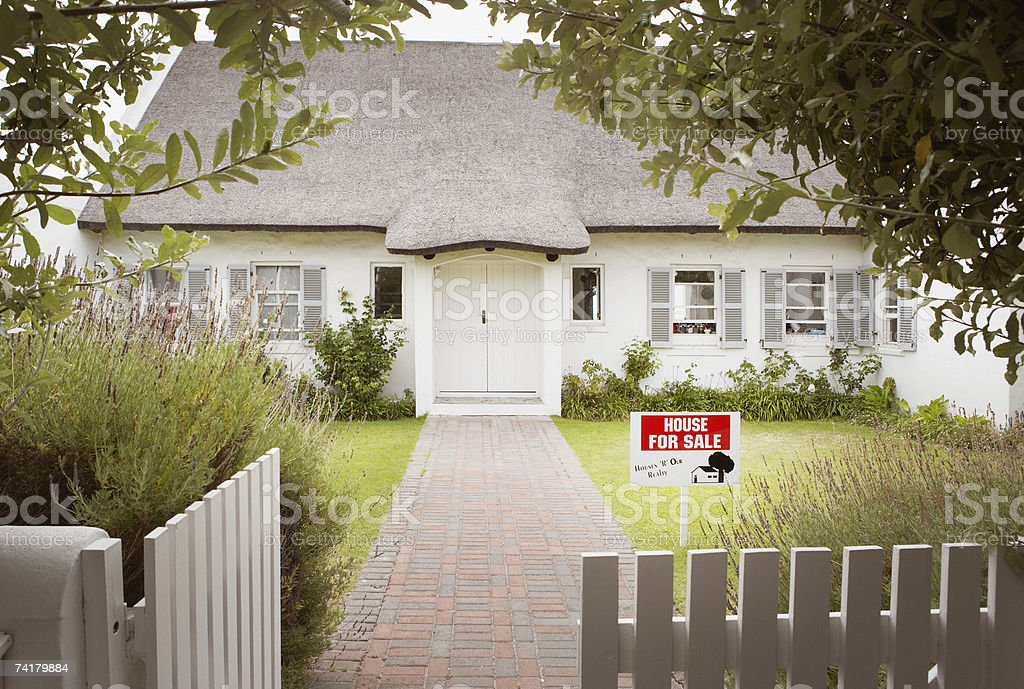 House with for sale sign in yard and open wooden fence stock photo