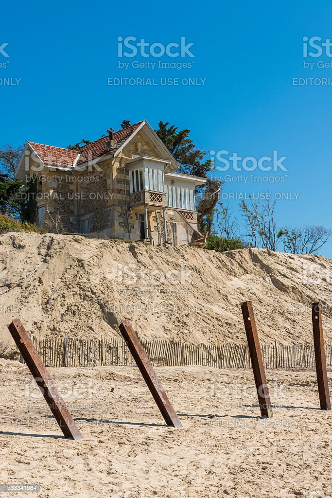 House with Poles and Erosion at Beach stock photo