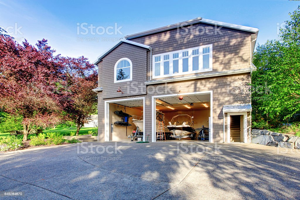 house with white trim and two motor boats in garage. stock photo