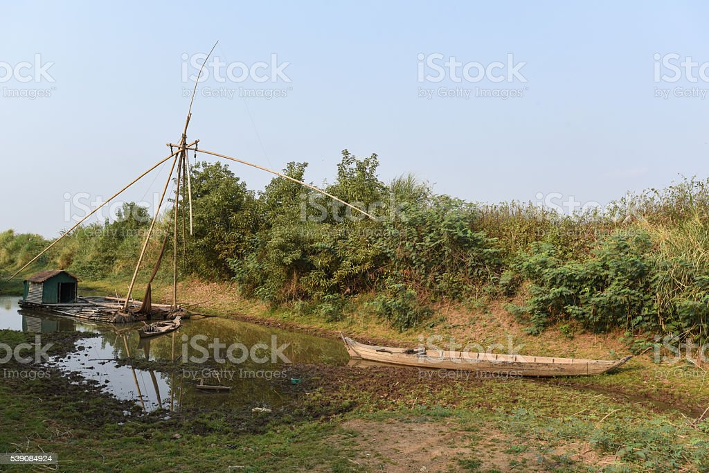 Houseboat with chinese fishing net and wooden dugout canoe stock photo