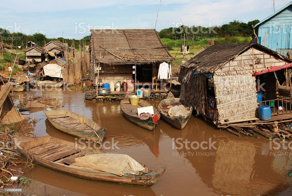 Houseboats on muddy water in Cambodia stock photo