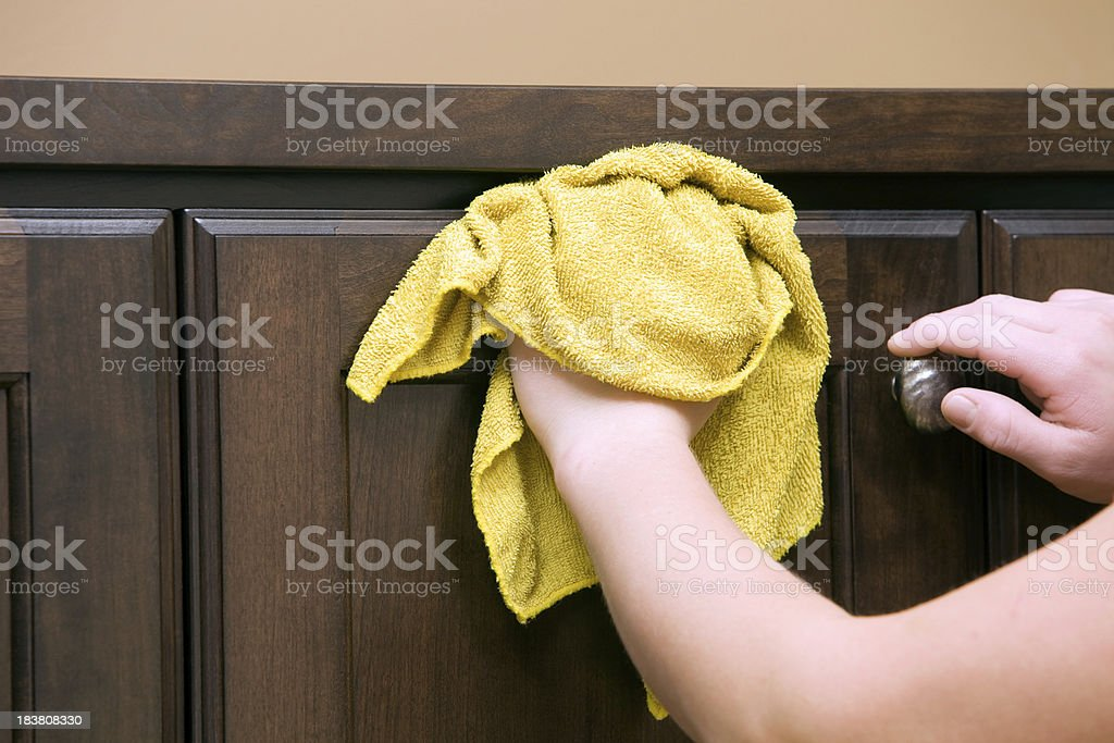 Housecleaner Wiping Dark Stained Cabinet stock photo