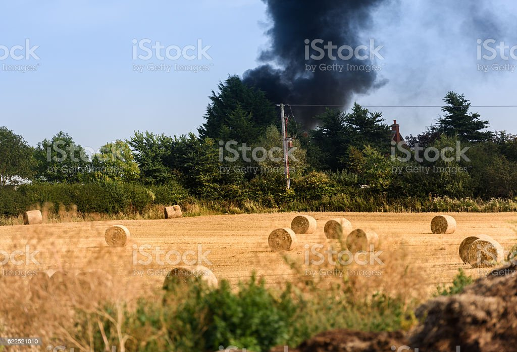Housefire in the distance after a field of rolled hay stock photo