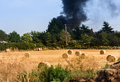 Housefire in the distance after a field of rolled hay