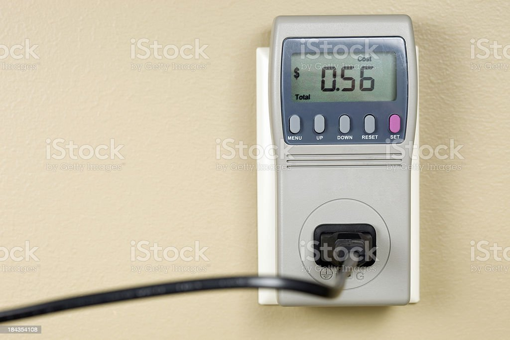 Household Killowatt-hour Monitor Plugged into Outlet and Appliance stock photo