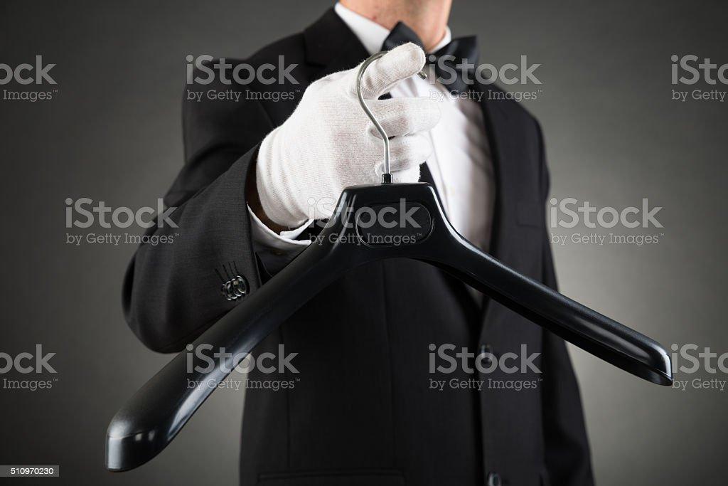 Housekeeper Holding Plastic Hanger stock photo