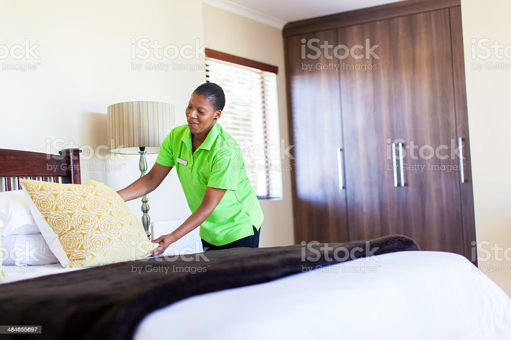 Housekeeper making a bed in the hotel room stock photo