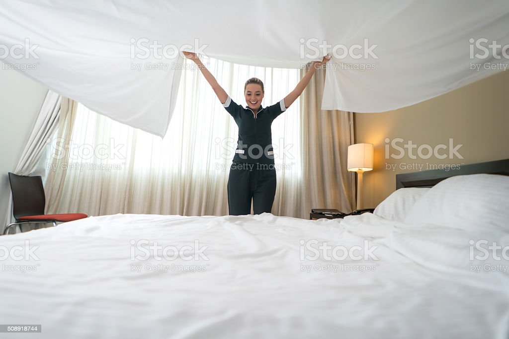 Housekeeper working at a hotel making the bed stock photo
