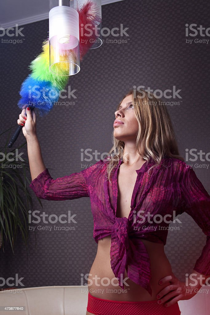 housemaid maid dusting on lamp stock photo