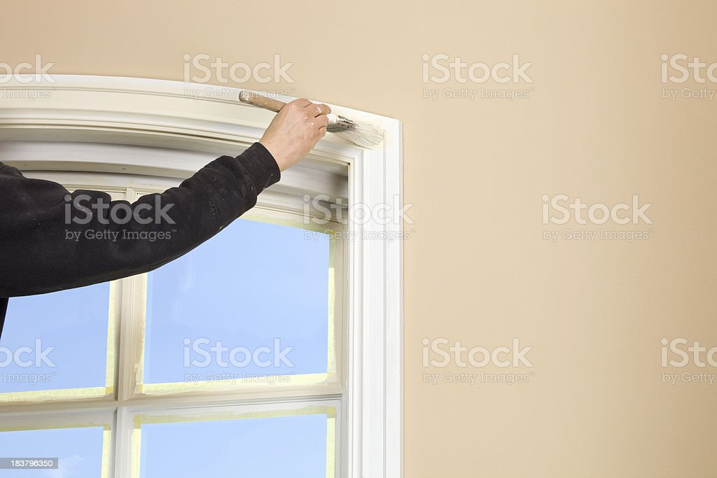 Housepainter Painting Window Trim with Blue Sky stock photo