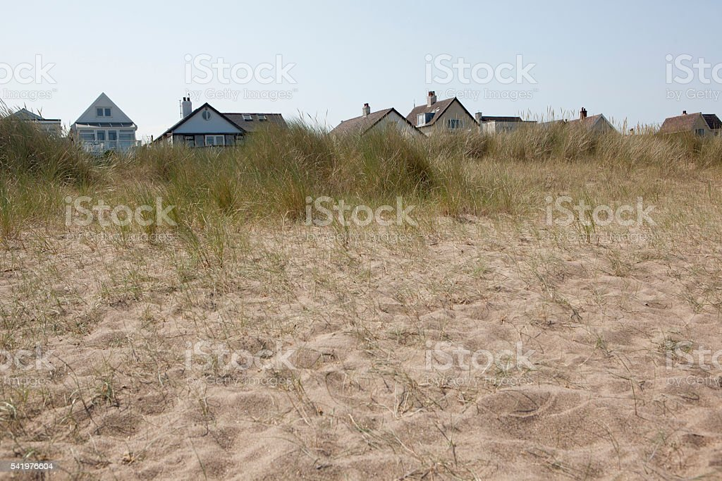 houses behind sand dunes stock photo