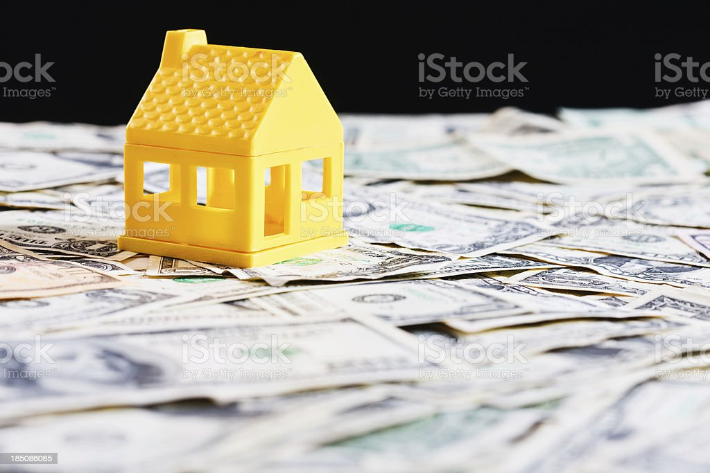 \'A model house rests on a field of US currency against a black...