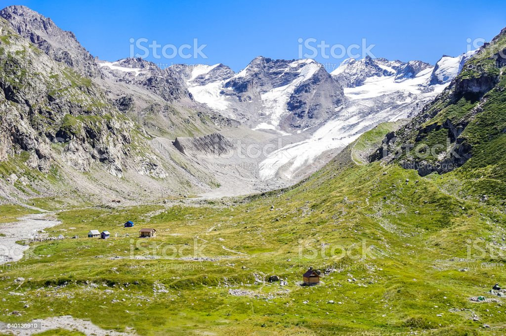 Houses in the valley at the foot of snow-capped mountains stock photo