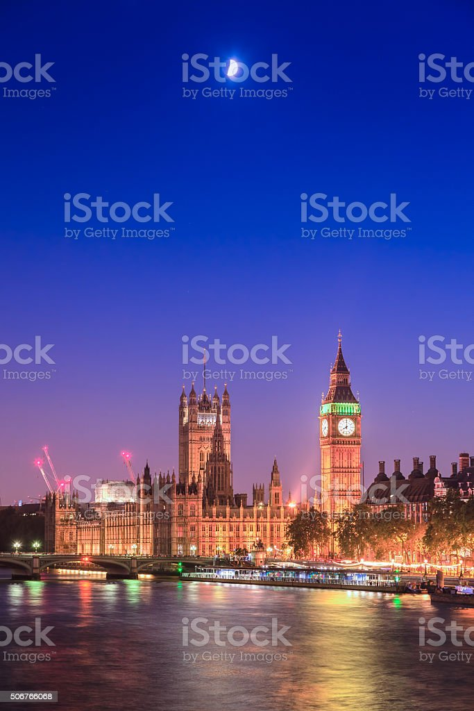 Houses of Parliament at night with moon, London, UK stock photo