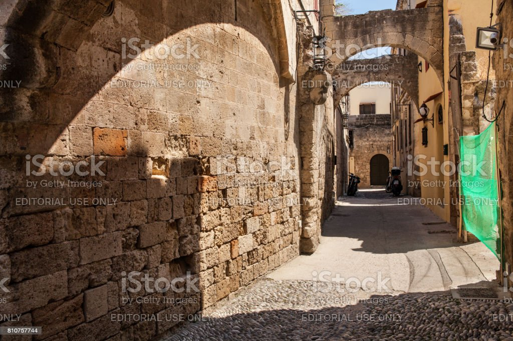 Houses of the locals and narrow streets in the city center in the Old Town of the capital of the island of Rhodes. stock photo