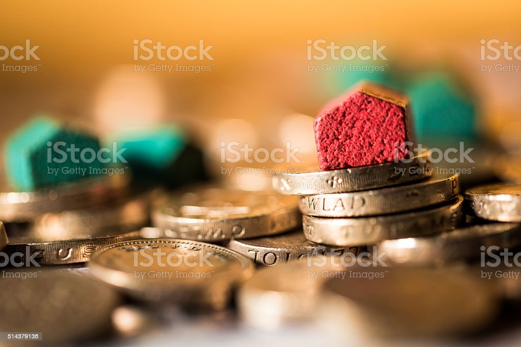 Houses on top of piles of money and coins stock photo