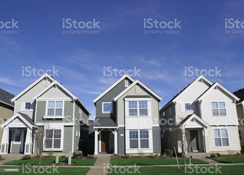 3 houses with 3 small front gardens against a clear blue sky stock photo