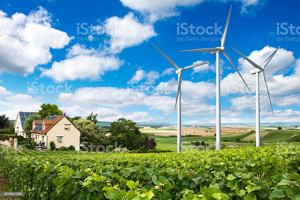 Houses with solar panels on roof and wind turbines stock photo