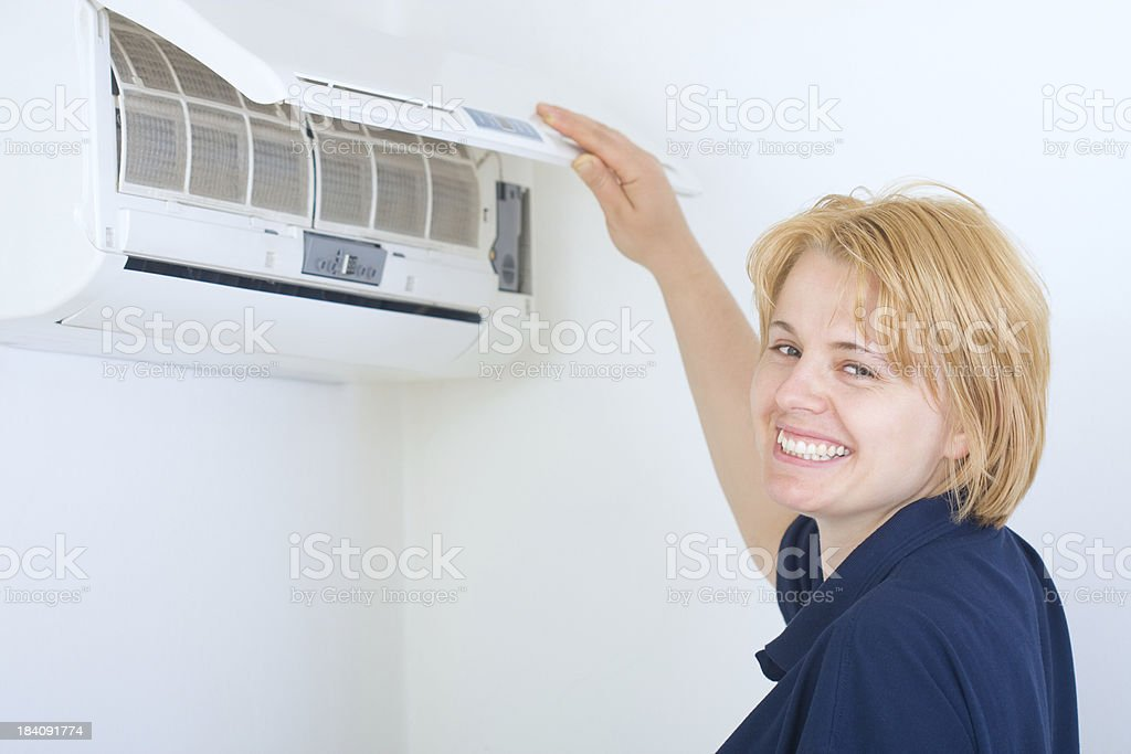 Housewife cleaning air conditioner stock photo