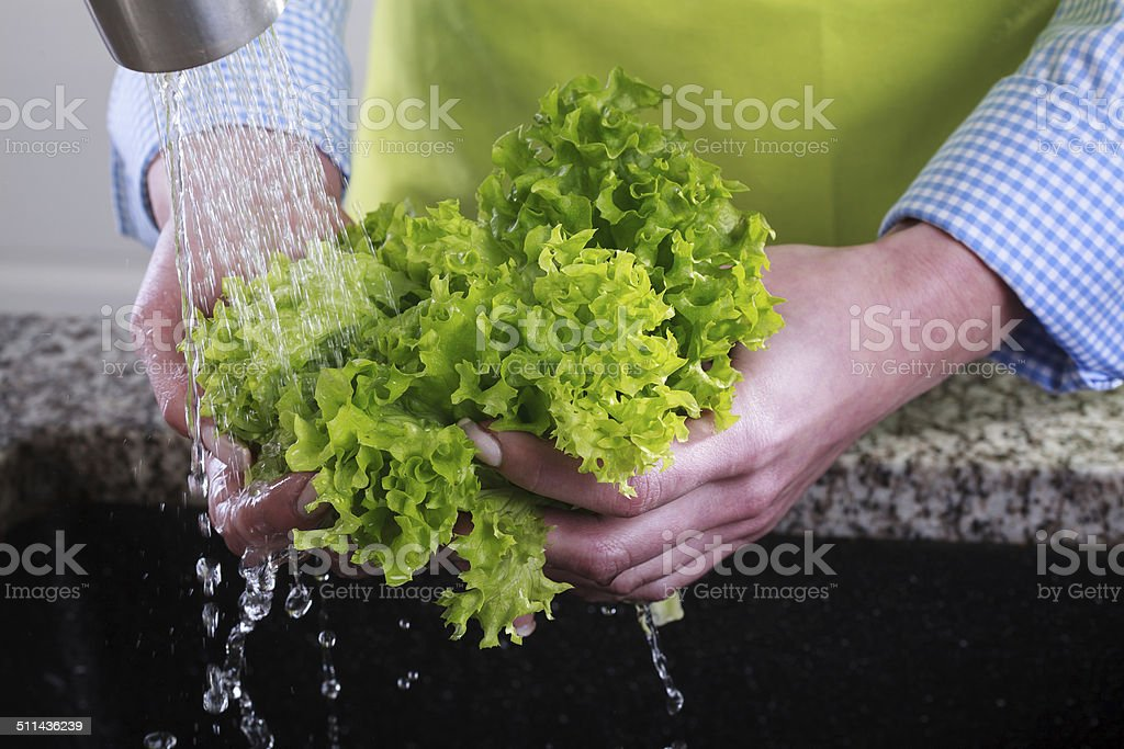 Housewife cleans a green salad stock photo