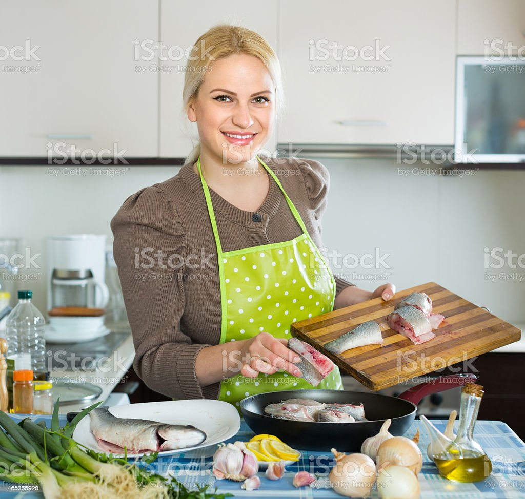 Housewife cooking fish at home stock photo