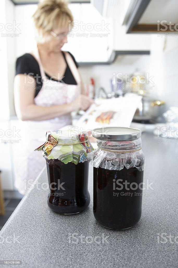 Housewife cooking in the kitchen homemade jam foreground royalty-free stock photo