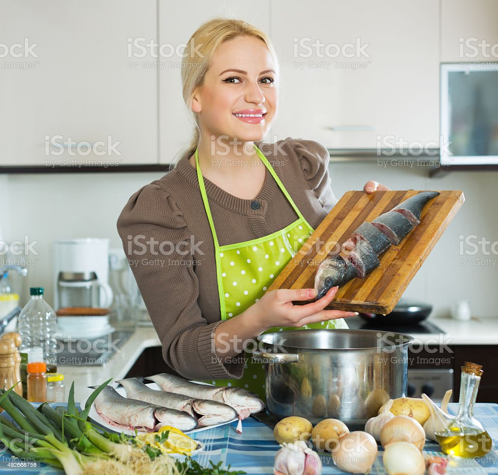 Housewife cooking soup with fish stock photo