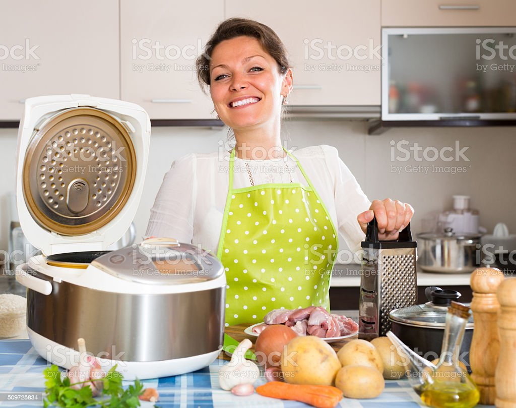 Housewife cooking with multicooker stock photo