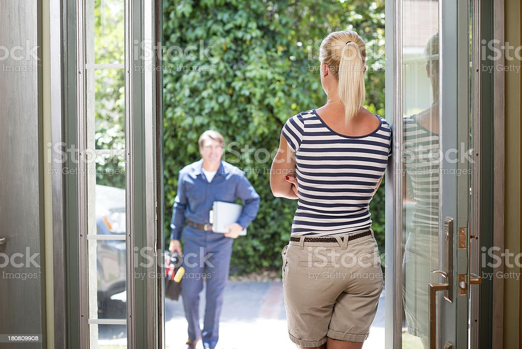 Housewife Greeting A Repairman In Uniform stock photo