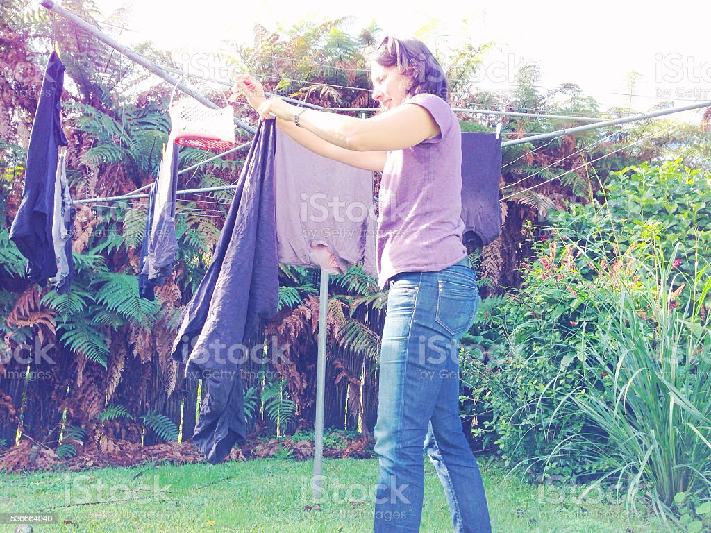 Housewife hanging washing on rotary clothes line stock photo