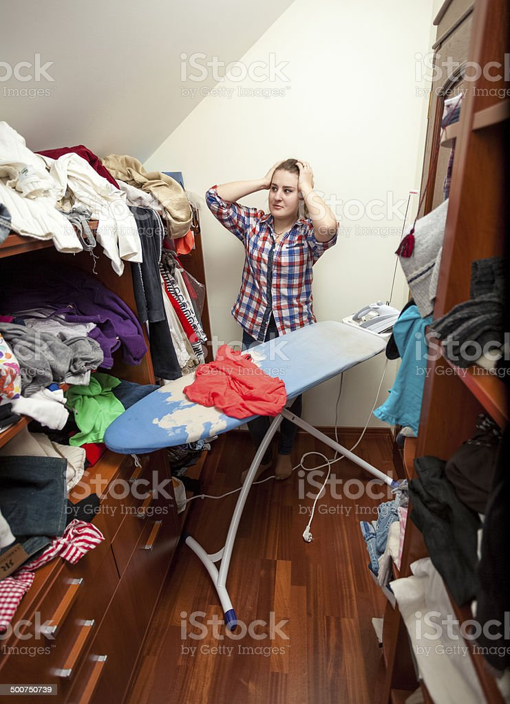 housewife having headache of big pile of not ironed clothes stock photo