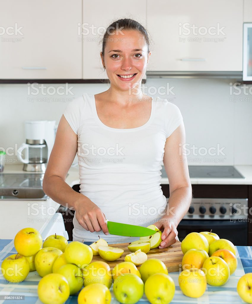 housewife in the kitchen with apples stock photo