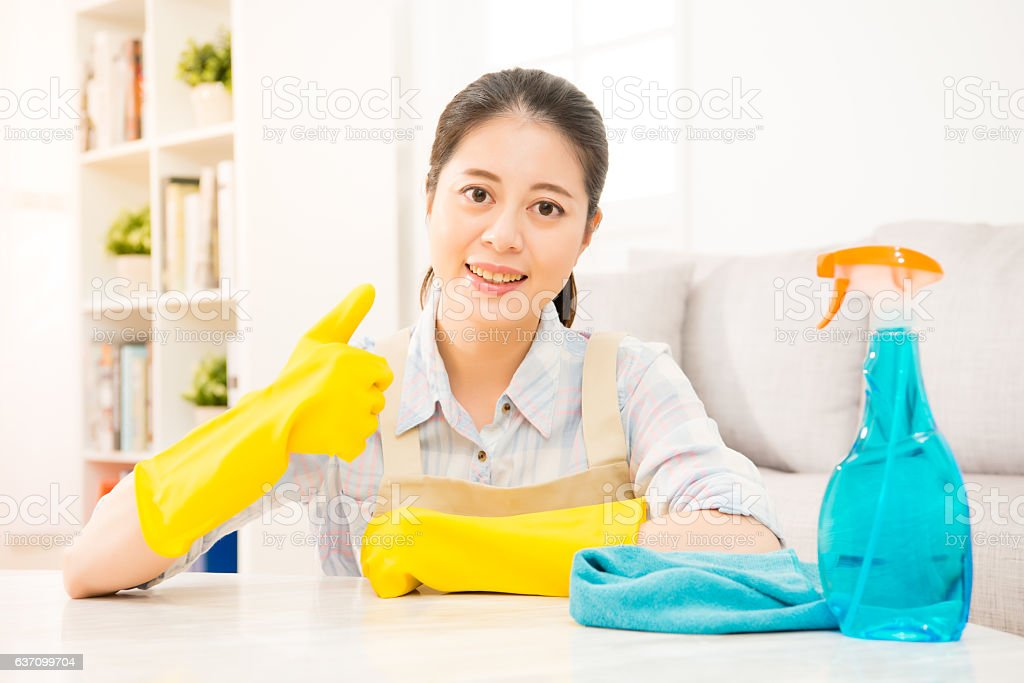housewife in yellow gloves showing thumbs up stock photo