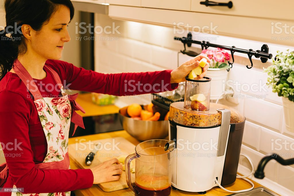 Housewife juicing at the kitchen stock photo