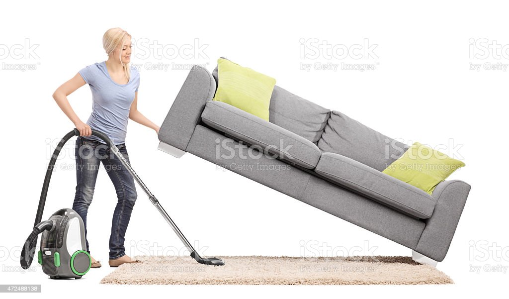 Housewife lifting a sofa and vacuuming underneath it stock photo