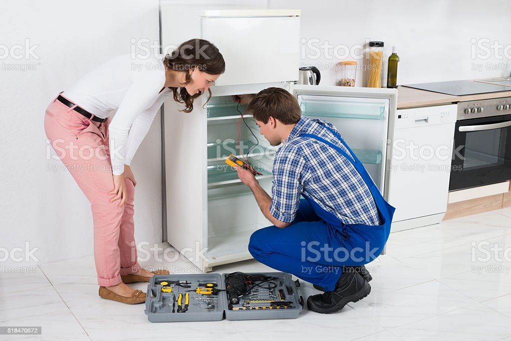 Housewife Looking At Worker Repairing Refrigerator stock photo