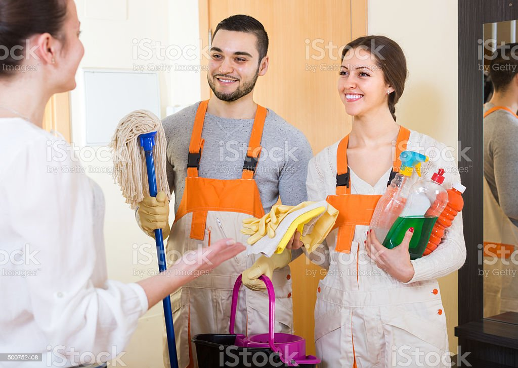 Housewife meeting cleaning crew at doorway stock photo