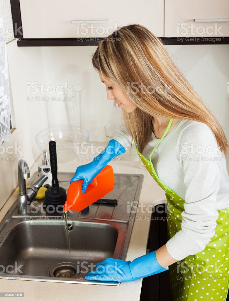 housewife pouring detergent into  sink royalty-free stock photo