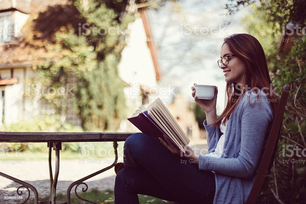 Housewife reading a book at the veranda stock photo