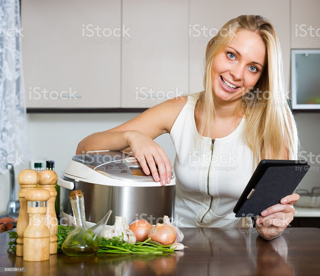 housewife reading ereader and cooking with multicooker stock photo