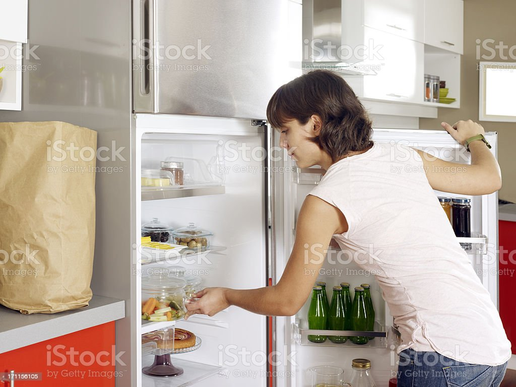Housewife refrigerator organizing stock photo