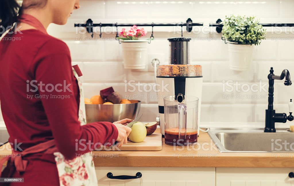 Housewife slicing fruits in the kitchen stock photo