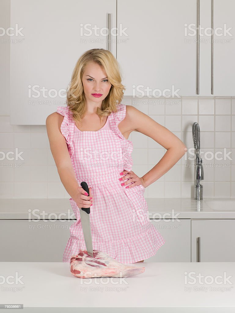 Housewife stabbing raw meat stock photo