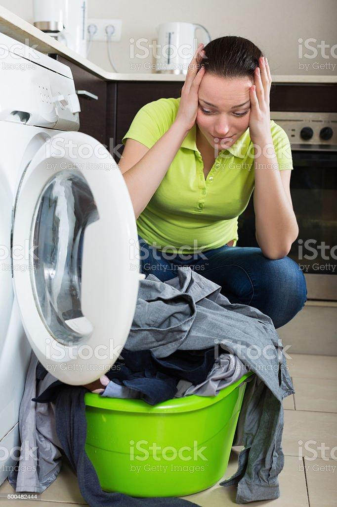 Housewife standing near washing machine stock photo