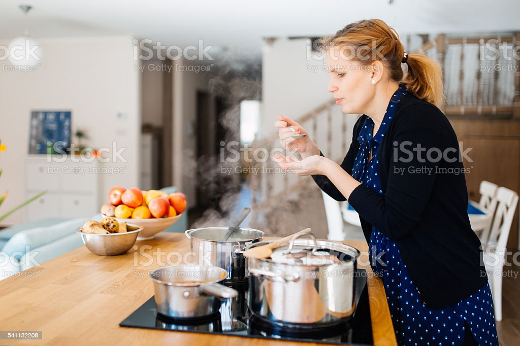 Housewife tasting food being made in kitchen stock photo
