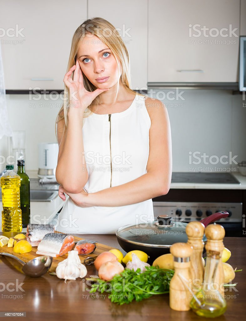 Housewife thinking what to cook for dinner stock photo