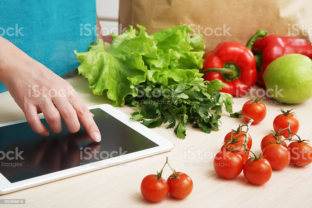 housewife uses a tablet computer in the kitchen stock photo