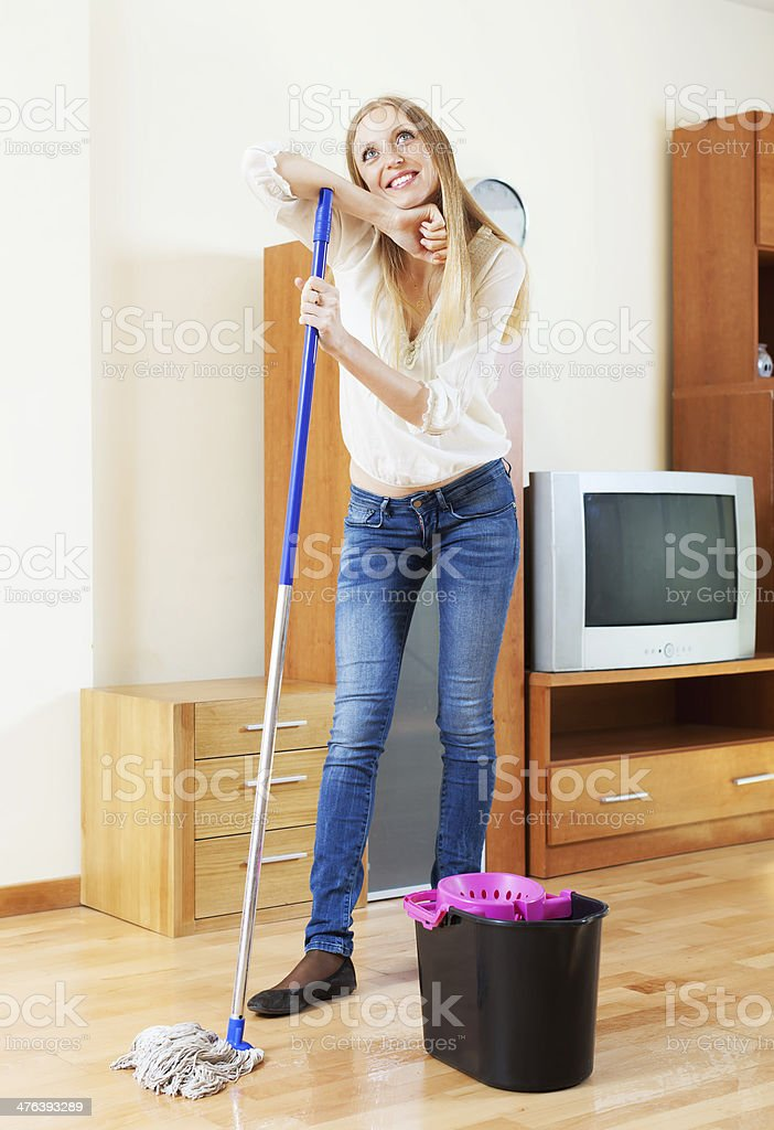 housewife washing parquet floor with mop  at home stock photo